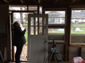Putting in a door with a window at the art cottage we are creating from a work shop