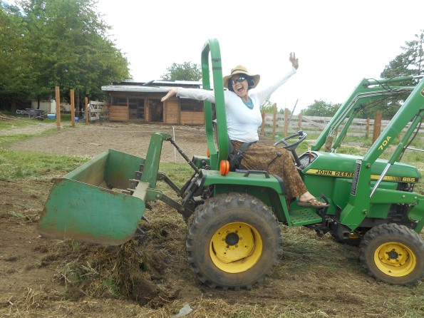 Me on the tractor grading the incline for the new corral and big barn